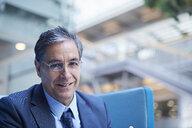 Portrait of mature businessman in office atrium - CUF06536