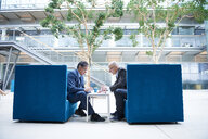 Two businessmen having discussion meeting in office atrium armchairs - CUF06542