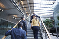 Rear view of businesswoman and men moving up office stairway - CUF06554
