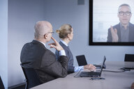 Businessman and woman watching office conference call - CUF06560
