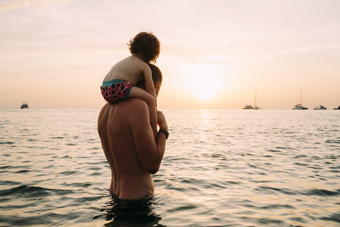 Back view of father carrying his little daughter on shoulders in the sea watching sunset - GEMF01973