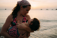 Mother holding little daughter on her arms in front of the sea by sunset - GEMF01979