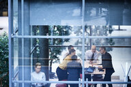 Window view of businesswomen and men having discussion in conference room - CUF06599