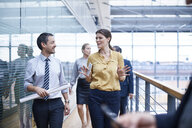 Businesswoman and men walking and talking on office balcony - CUF06605