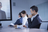 Businesswoman and man smirking during office conference call - CUF06611