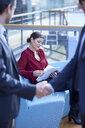 Businessmen shaking hands looking at businesswoman reading paperwork in office atrium - CUF06626