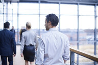 Rear view of businessmen and woman walking on office balcony - CUF06695