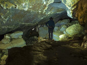 Spain, Basque Country, Euskadi, senior man viewing rocks in Baltzola cave - LAF02039