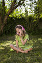 Portrait of girl sitting on meadow listening music with headphones and smartphone - LVF06981