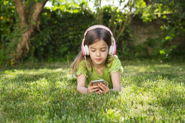Portrait of little girl lying on meadow listening music with headphones using smartphone - LVF06984