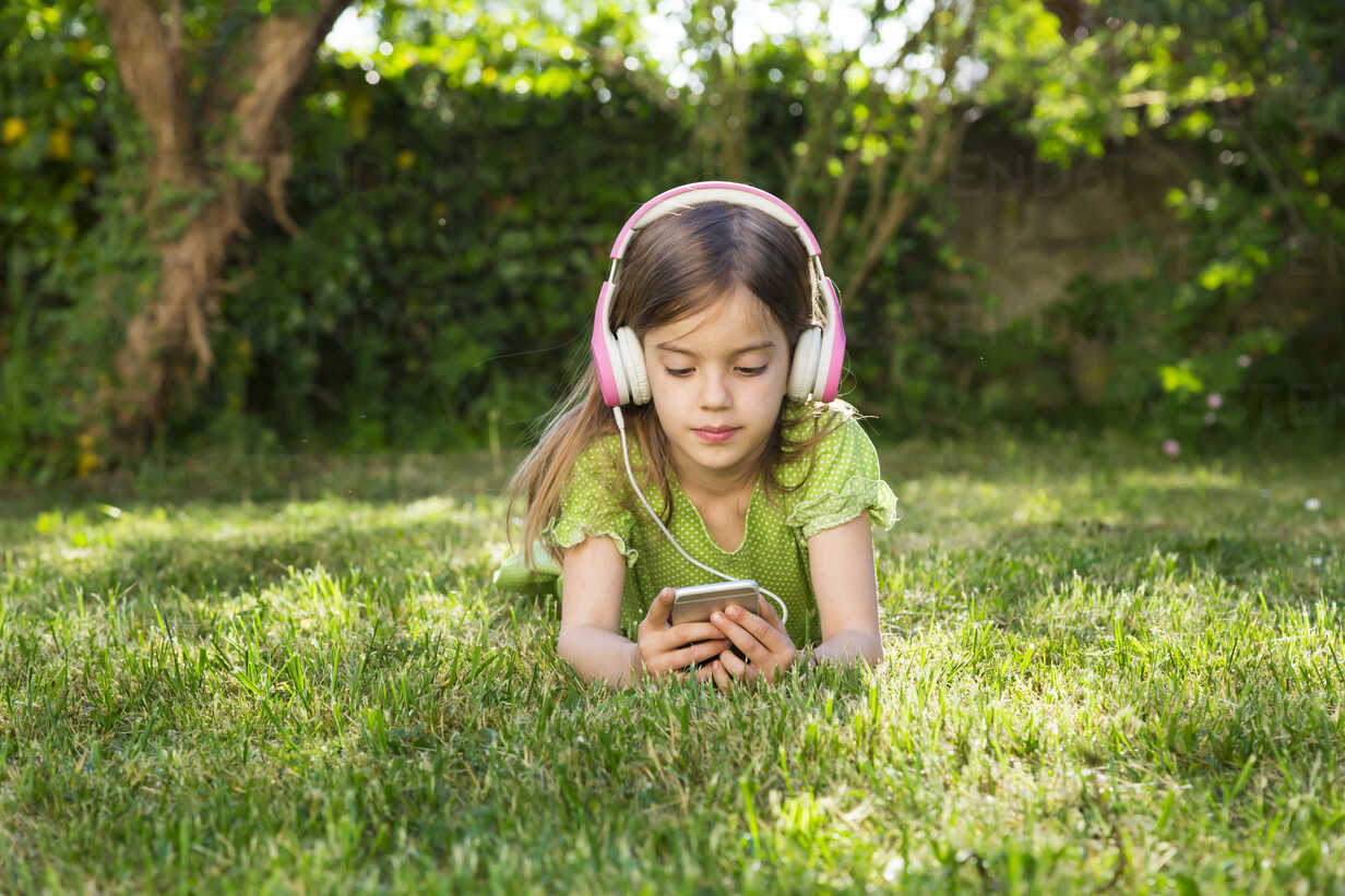 Portrait of little girl lying on meadow listening music with headphones using smartphone - LVF06984 - Larissa Veronesi/Westend61