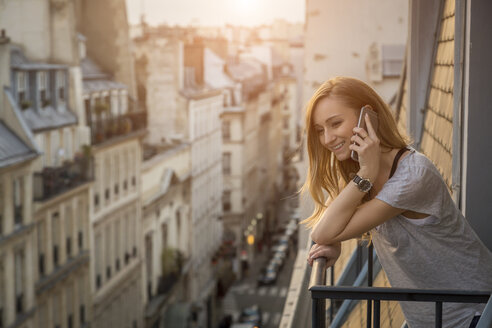 France, Paris, portrait of smiling woman on the phone standing on balcony in the evening - JUNF01045