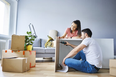 Couple in new apartment assembling furniture together - BSZF00411