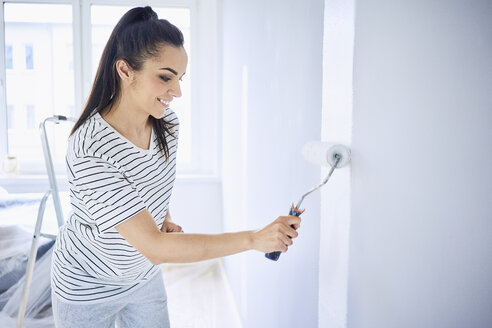 Smiling woman painting wall in apartment - BSZF00417