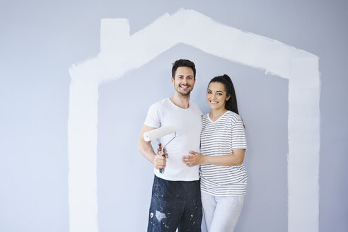 Portrait of happy couple painting in new apartment with house shape on wall - BSZF00420