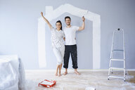 Portrait of cheerful couple painting in new apartment with house shape on wall - BSZF00423