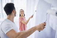 Happy couple painting wall in apartment together - BSZF00426