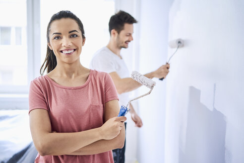Portrait of happy woman painting wall with boyfriend in new apartment - BSZF00429