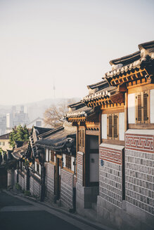 South Korea, Bukchon Hanok Village, street with traditional houses, Seoul Tower in the background - GEMF01987