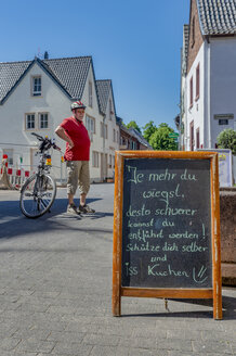Germany, Zons, senior man with bicycle having a rest - FRF00660