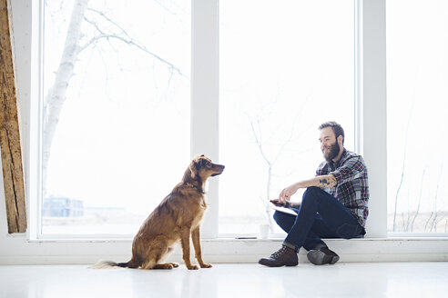 Young male designer with dog in design studio window seat - CUF06863