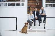 Portrait of male and female design team sitting on design studio stairs - CUF06914