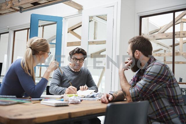 Female and male designers brainstorming at design studio desk meeting - CUF06929