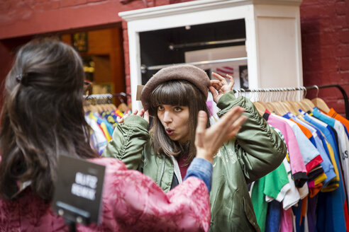 Two young women trying on beret at vintage clothes stall - CUF06965