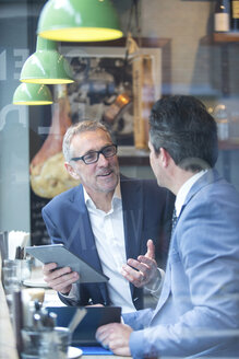 Two businessmen having discussion in restaurant window seat - CUF07046