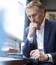 Mature businessman using digital tablet in restaurant window seat - CUF07052