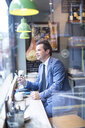 Mature businessman with smartphone in restaurant window seat - CUF07055