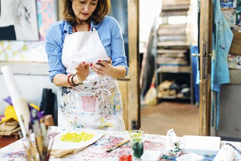 Mature woman in creative studio, using smartphone - CUF07085