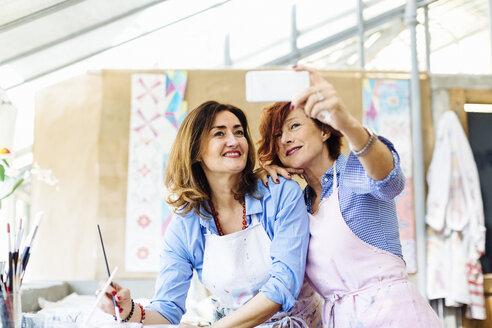 Two women in creative studio, taking selfie, using smartphone - CUF07091