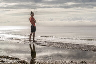 Man on shoreline looking away at view of sea - CUF07148
