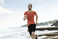 Young male runner running along beach - CUF07160