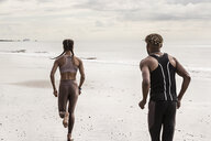 Rear view of young male and female runners running on beach - CUF07172