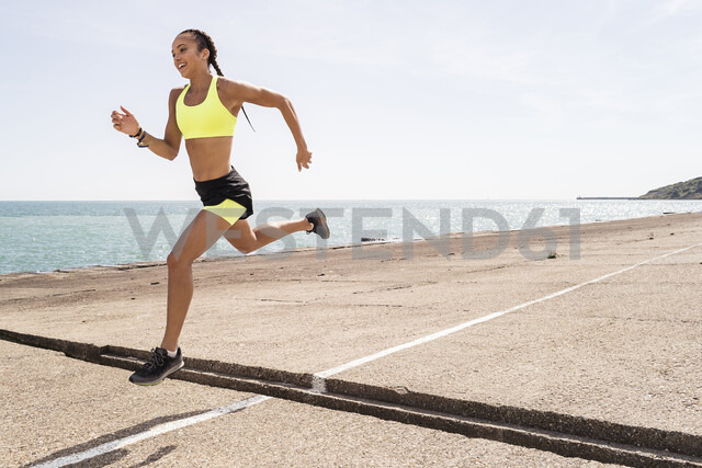Young woman running outdoors, jumping over gap in bridge, mid air - CUF07181