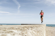 Young woman running along sea wall, mid air - CUF07187