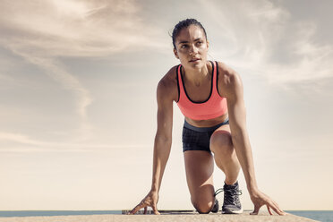 Young woman on sea wall, in start position, preparing for run - CUF07190