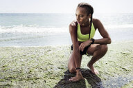 Young woman wearing sports clothing, crouching on beach - CUF07208