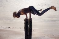 Young man training, doing handstand on wooden beach posts - CUF07214