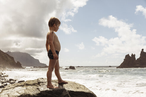 Young boy standing on rock, looking at view, Santa Cruz de Tenerife, Canary Islands, Spain, Europe - CUF07238