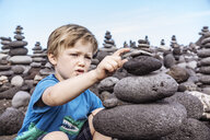 Young boy examining stack of rocks, Santa Cruz de Tenerife, Canary Islands, Spain, Europe - CUF07241