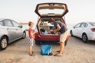 Father and son taking fishing rods from car boot, Goleta, California, United States, North America - CUF07244