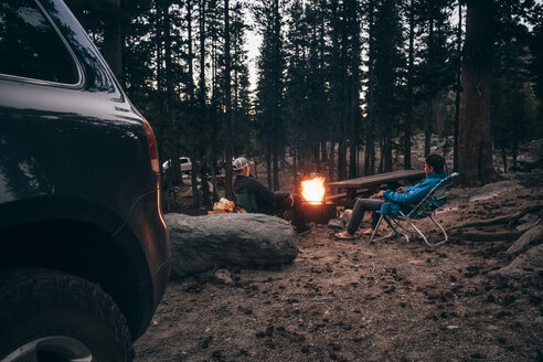 Friends camping in forest by campfire, Mammoth Lake, California, USA, North America - CUF07256