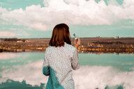 Woman blowing bubbles, cloudscape reflection in lake, Ural, Sverdlovsk, Russia - CUF07283