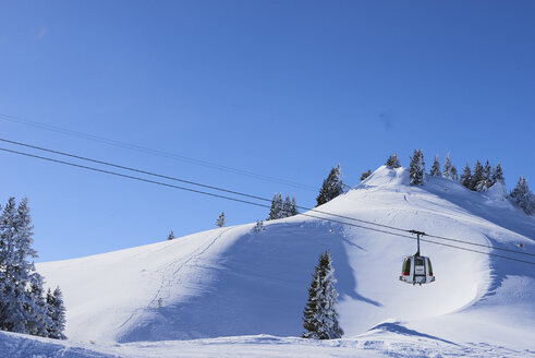 Cable car in snow covered mountain landscape, Gstaad, Switzerland - CUF07355