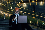 Mature businessman outdoors at night, sitting on steps, using laptop, holding smartphone - CUF07478