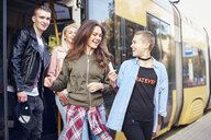Four young adult friends exiting city tram - CUF07487
