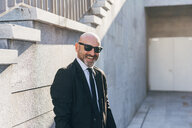 Portrait of mature businessman outdoors, standing beside steps, smiling - CUF07499